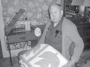 """Wendell Griffith displays one of his favorite quilts he made with his leaf pattern. """"My mother taught me to quilt,"""" said Griffith. (AP Photo/The Daily Enterprise, Nola Sizemore)"""
