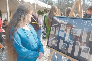 """REMEMBERED AFTER 34 YEARS — Rose Kelley, of Cincinnati, Ohio, looked at a display of old newspaper clip- pings Tuesday detailing information about underground coal miners who were killed during twin explosions at Blue Diamond Mining Co.'s Scotia mine at Ovenfork in Letcher County, which occurred 34 years ago this week. Kelly was among a crowd of about 300 who attended the unveiling of a historical marker erected in honor of the 26 miners who were killed. Kelley's brother, Kenneth """"Doyle"""" Turner, and her cousin, Willie D. Turner, both died in the first mine explosion, which occurred at 11:45 a.m., on March 9, 1976. Kelley's father, Grant Turner, was working in the mine that day but survived. Her brother, Claude Turner, helped recover rescue workers killed in the second blast, which occurred at approximately 11:30 p.m. on March 11, 1976. More photos of Tuesday's ceremony can be viewed for free by following the links at www.themountaineagle.com. (Photo by Sally Barto)."""
