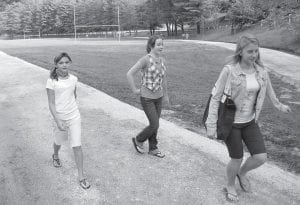 "FIRST WALK AROUND THE TRACK — Pictured from left, sixth-grade students McKenzie McIntyre, Brooklynn Madden, and Meggan Johnson took a walk around the then justcompleted walking track at Beckham Bates Elementary School at Colson. The track has a front loop that covers the entire ground around the front of the building, as well as a connecting loop that goes around the back part of the campus. The county road department did the construction work, with all gravel donated by EQT. The only expense to the school was a ""felt-like"" material put down to keep grass from growing through the gravel. Funds for that material came from a ""Lowe's Toolbox"" grant."
