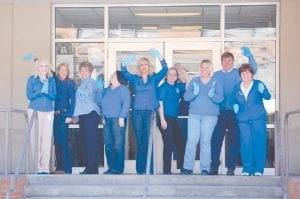 DANCING TO RAISE AWARENESS — Several people who work in the Letcher County Courthouse wore blue-colored clothes on March 5 and danced in front of the courthouse as part of Colon Cancer Awareness Month. Nell Fields, project manager with Faith Moves Mountains, and Robert Salyer, a videographer at Appalshop, spent the morning videoing people dancing at diff erent locations in Whitesburg. The footage will be made into a video that will eventually be placed on YouTube. Pictured from left are Courtney Baker, judicial secretary for Letcher District Judge Kevin R. Mullins, Ann Adams, courthouse maintenance supervisor, Hettie Adams, executive secretary for Letcher County Judge/Executive Jim Ward, D.J. Frazier, county finance officer, Lisa Maggard, deputy clerk, Nell Fields, project manager for Faith Moves Mountains, Tiff any Bowling, deputy circuit court clerk, Letcher County Judge/Executive Jim Ward and Teressa Day, deputy circuit court clerk.