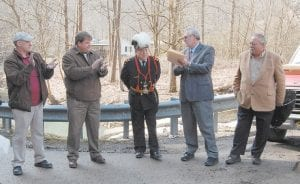 BIRTHDAY SURPRISE — A sign was unveiled on March 4 dedicating Sergent Loop after Arius Holbrook, of Sergent, on his 67th birthday. Arius Holbrook's brother, Darrell Holbrook of Kona, had asked the Letcher County Fiscal Court to approve his request to dedicate the road in honor of his brother at the February court meeting. Arius Holbrook is a right eminent grand commander of the Grand Commandery of Knights Templar of Kentucky, the top ranking Masonic organization in the York Rite of Freemasonry. The main philanthropy of the Grand Commandery of Knights Templar focuses on providing eye surgery to those who could not otherwise afford it. Pictured above at the uveiling were, from left, District Three Magistrate Codell Gibson, Letcher County Judge/Executive Jim Ward, Arius Holbrook, Letcher County Attorney Harold Bolling and Darrell Holbrook. (Photo by Sally Barto)