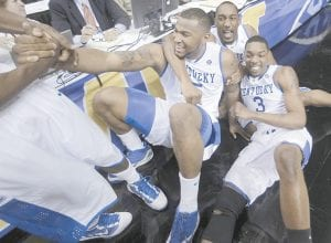DeMarcus Cousins, center, was helped up off the court as he celebrated with Ramon Harris, top right, and Darnell Dodson, right, after Cousins scored at the buzzer to send the championship game into overtime. (AP Photo/ Dave Martin)