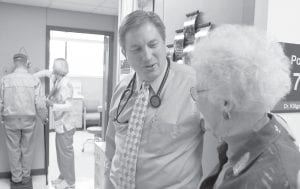 Primary care physician Dr. Don Klitgaard greeted Muriel Bacon as her husband weighed in with a nurse at the Myrtue Medical Center in Harlan, Iowa, recently. Lines to see physicians such as Klitgaard could get longer under the landmark health overhaul signed into law. (AP Photo)