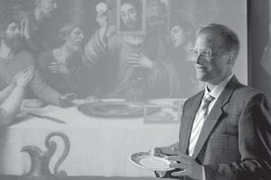 """In this photo provided by Cornell University, Prof. Brian Wansink, holds a plate illustrating how food portion size has grown over the centuries while standing in front of a projection of Vicente Juan Masip's (also known as Juan de Juanes) """"The Last Supper."""" (AP Photo/Cornell University)"""
