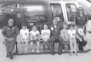 GIRL SCOUT BROWNIE TROOP 1314 enjoyed a recent visit to Wings Air Rescue. The girls learned about the helicopter and first aid, and took turns sitting in the helicopter and trying on the night vision goggles. They even practiced first aid on each other. Pictured are (left to right) Scott Campbell, Amy Stamper, Hanna Bates, Cammy Elswick, Tom Savage, Luna Combs, Amanda Stamper, MaKaya Rose, and Shane Dingus. Not pictured is Maddison Pennepacker.