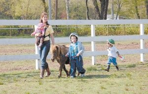 """HORSIN' AROUND — Leah Baldwin (left) carried her daughter, Anna Belle, while walking a horse with Mark Howard at The Stables at Creekside Glen in Partridge, a """"stable ministry"""" which works with at-risk children. Mrs. Baldwin's son Boone followed closely behind. (Photo by Sally Barto)"""