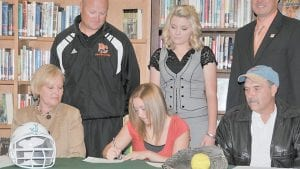 CONTINUING THEIR CAREERS — Jenkins Lady Cavaliers softball player Emily Walker and volleyball player Lauren Sparks have signed college scholarship off ers with Pikeville College. In the photo at left, Walker inks her off er while her father, Joe Walker (front right), of McRoberts, and mother, Pam, look on. In photo at right, Sparks signs her scholarship off er while a smiling Pikeville volleyball coach Anna Bevins watches. (Photos by Chris Anderson)