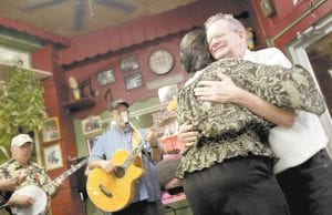 Ernie Shinault gave a hug to Vicki Lynn Smith after the two danced on Smith's birthday (April 6) at Curbside Coff ee's Bluegrass Night in Cleveland. (AP Photo/The Plain Dealer, Gus Chan)