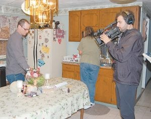 FILMING A 'PILOT' — A cameraman filmed Verlin Short on May 11 as he cleaned the kitchen table and his wife, Reva, washed breakfast dishes. The couple as well as their four children will be featured in a pilot on Animal Planet in about six months. The show will explore Verlin Short's hobby of catching snakes. (Photo by Sally Barto)