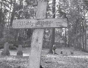 """Linda Fitzgerald, with the Seattle Genealogical Society, checks one of two known and marked African-American coal-miner graves at Newcastle Historic Coal Miner's Cemetery in Newcastle, Wash. The cemetery is the kind of place familiar to a few local kids and invisible to most everyone else. It's tucked up on a hill and secured by a locked gate. The closest most visitors get is a sign that says """"King County Historical Site."""" (AP Photo/The Seattle Times, Alan Berner)"""