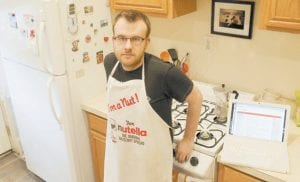"""Brian Kraus, who hosts a food blog, poses in his kitchen in Albany, N.Y. Kraus loves to cook but has only one cookbook. When Kraus wanted tips on preparing a whole fish, he headed to the Web and did a """"mishmash"""" of stuff he liked from diff erent sites. (AP Photo/Mike Groll)"""