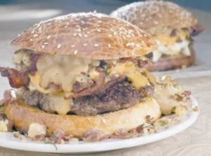 Spike Mendelsohn's truly ingredient packed 24/7 burger, which includes egg, corned beef hash and bacon. (AP Photo/ Larry Crowe)