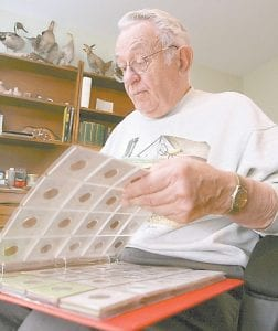 """Charlie Fulker looks through a book of Lincoln pennies in his home in Bath, S.D. He collects old and new coins, cataloging the important ones. """"This hobby — it's a great time for an old guy,"""" said Fulker, 79. """"It gives me something to do."""" (AP Photo/Aberdeen American News, John Davis)"""