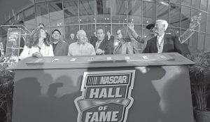 From left, Teresa Earnhardt, Ron Hornaday, Jr., Jack Ingram, Darrell Waltrip, Lisa France Kennedy, Brian France (behind Lisa France Kennedy), Richard Petty, rear right gesturing, and Junior Johnson, reacted as they officially opened the NASCAR Hall of Fame in Charlotte, N.C., on Tuesday. (AP Photo)