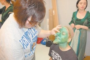 """NOSE JOB — Meagen Arrowood is being transformed into the wicked witch this week as the Letcher County Central High School drama class performs """"The Wizard of Oz"""". Kim Sergent, a history teacher at LCCHS, held onto a prosthetic nose as she put more green makeup on a sponge. The prosthetic nose, chin and wart were made by Whitesburg dentist, Dr. David Narramore. Public performances of """"The Wizard of Oz"""" will begin at 7 p.m. on Friday and Saturday nights. (Photo by Sally Barto)"""