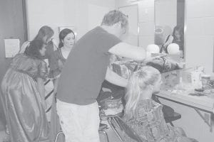 """VOLUNTEERING HIS SERVICES — Keith Adams, owner of The Looking Glass Beauty Salon, styled Hailey Kuracka's hair earlier this week. Adams is one of several community members who volunteered his time to help the Letcher County Central High School drama class in their spring production """"The Wizard of Oz""""."""