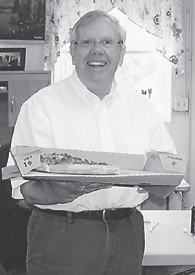 PIZZA PARTY — Jim Craft serves pizza at the Ermine Senior Citizens Center. The Ermine senior citizens won the pizza party by collecting more money for the Relay for Life than any other center in the county.