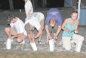 Letcher County Relay For Life volunteers lit candles in memorials to remember cancer victems and honor survivors. Here, from left, Kenny Spangler, Gaither Frazier, Seth Collins and Bambi Pelham light the memorials.