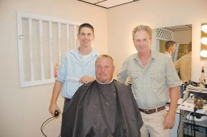 LIKE FATHER, LIKE SON — Thirty-year-old Kevin Brown (pictured at left) recently started working with his father, Richard Brown, who owns Cut-Away Barber and Beauty Salon. Richard Brown has been cutting hair in Whitesburg for 42 years. About 20 years ago, Richard Brown cut actor Ned Beatty's hair for a week when he was in Letcher County filming at Appalshop. Cecil Sexton is pictured getting a haircut.