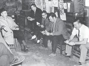 """It appears that Mr. Ed Moore is serving as the choir leader for these singers in the furnace room (later called """"The Snake Pit"""") in their gathering before classes start. Members are from the back: Mr. William (Trim) Richardson, Mr. P.M. Armstrong, Mr. Gerald Frazier and Mr. Buddy Roe."""