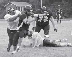 Wolves running back Matt Maggard broke a pair of tackles on this rushing attempt to gain the first down in the 6-0 win over Pike County. He was aided by teammate Corey Harris, at right. (By Chris Anderson)