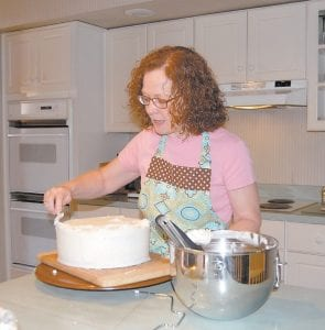 Since retiring from her job as school teacher, Bonnie Adams has been perfecting her hobby of baking cakes and decorating them with fondant icing. Here, Adams works on a cake in the kitchen of the Letcher home she shares with her husband, Martin. (Photo by Sally Barto)