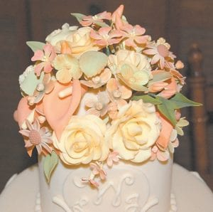 Handmade sugar flowers decorate the top of a three-tiered wedding cake which earned Adams a blue ribbon at the Kentucky State Fair.