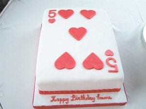 A birthday cake decorated with the five of hearts.