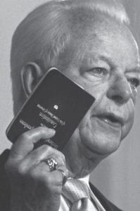 """Sen. Robert Byrd held a copy of the Constitution he kept in his pocket as he spoke at the launching of his book """"Losing America: Confronting a Reckless and Arrogant Presidency,"""" in 2004. A de facto parliamentary overlord, Byrd sought most broadly to restrain the power of the presidency, for America has no monarch, and to protect the minority party in the Senate from being crushed by the majority. (AP Photo)"""