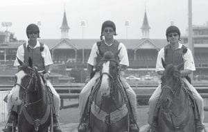 Outriders Shawn Brasseaux, left, Greg Blasi, center and Lee Lockwood posed for a photo before taking the track at Churchill Downs in Louisville. (AP Photo/The Courier-Journal, Michael Clevenger)