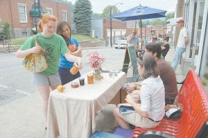 CHECKING OUT THE GOODS — Janney Lockman, an Appalshop intern from Green Bank, W.Va., held a can of pickled carrots while Jocelyn Streit, a Faith Moves Mountains intern from St. Louis, Mo., stood beside her on Main Street in Whitesburg at the Letcher County Farmers Market on July 17. Lark and David McMillan-Fields, who are pictured sitting on the bench, would like to see more people sell produce and other items at the farmers market.