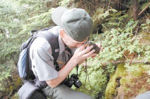 Biologist Glenn Taylor uses a hand lens to search for the spruce-fir moss spiders in the Great Smoky Mountains National Park. The federally endangered spider is one of the world's smallest tarantulas, measuring three millimeters. (AP Photo/ Knoxville News Sentinel, Amy Smotherman)