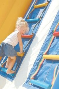 Two-year-old Ava Potter climbed the ladder of an inflatable attraction during the Letcher County Kids Day Back to School Bash at River Park in Whitesburg last week. Ava is the daughter of Virginia Potter and Jeremy Ritchie of Kona. The inflatable was operated by X-Treme Fun of Whitesburg. Organizers of the Back to School Bash said that local businesses paid for 1,800 backpacks which were filled with school supplies and given to children attending the event. (Photo by Sally Barto)