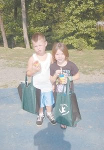 Above, Trey and Mercedes Little posed for a photo during the Letcher County Kids Day Back-to-School Bash held July 23 at River Park in Whitesburg. Trey, 8, and Mercedes, 6, enjoyed walking around the park eating slushies and getting free goodies. The siblings, who attend West Whitesburg Elementary School, are the children of Shelly Little and Bryce Baker of Pine Creek. Below, three-year-old Morgan Branham held on as Letcher District Judge Kevin R. Mullins guided the horse, Silver. Morgan is the daughter of Raymond and Tracey Branham of McRoberts. (Photos by Sally Barto)