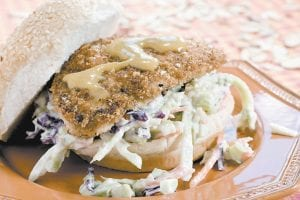 A honey Dijon beermarinated chicken sandwich with slaw is seen in this photo. Beer provides a great, effortless way to impart flavor and moisture to chicken. (AP Photo/ Larry Crowe)