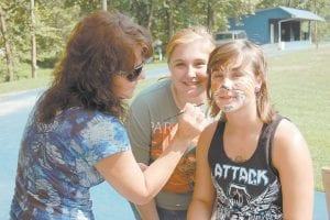 Mona Rae (left) of Neon painted the face of 15-year-old Annie Boggs of Cumberland. Also pictured is Sara Boggs of Cumberland.