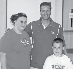 BASKETBALL CAMPER — Hunter Jackson, 7, attend John Calipari's Pro Camp at Memorial Coliseum in Lexington July 28-30, where he was recognized as Camp Player of the Day. During the camp, Hunter met former University of Kentucky basketball players DeMarcus Cousins, John Wall, Eric Bledsoe, and Patrick Patterson, who were there daily. Hunter's sister, Amber, attended the camp as an observer. Hunter is a second grade student at Arlie Boggs Elementary School and plans to attend the camp again next summer. Hunter and Amber are the children of Arf and Faith Jackson of Partridge. They are pictured with UK Coach John Calipari.