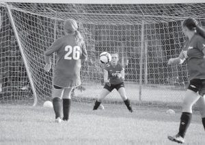 Letcher County Central High School goal keeper Erica Meade focused on catching the soccer ball after Savannah Hampton kicked it during a camp conducted by Morehead State University on Aug. 5 at the old Whitesburg High School football field.