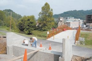 BETTER BRIDGE — City of Whitesburg employees Greg Collins (left) and Adam Caudill were busy Aug. 17 working on new concrete steps which will make it easier for people to walk from the free city parking lot to the James W. Bates Pedestrian Bridge. (Photo by Sally Barto)