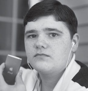 Matthew Brady, 17, of Foxborough, Mass., posed for a portrait in his home while wearing ear phones and displaying an iPod. (AP Photo)