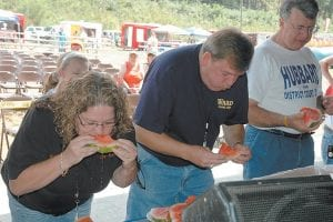 FESTIVAL SEASON IN FULL SWING — Letcher County Judge/Executive Jim Ward (center) ate 21 pieces of watermelon to win a watermelon eating contest at the Riverside Days festival held in Whitesburg over the weekend. Shown competing against Ward are Whitesburg City Council Member Shelia Page-Shortt (left) and Asst. Letcher County Attorney James Hubbard. Riverside Days is the first of a series of festivals held each year in Letcher County. The Jenkins Homecoming Days Festival begins this week.