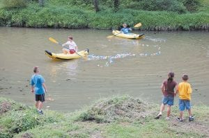 Clay Jenkins, 8, (left), Kandis Jenkins, 7, and Will Hollon, 8, watched Eric Fields and Noah Brosmer as they paddled in inflatable kayaks in the Kentucky River at River Park in Whitesburg on Aug. 21. Fields and Brosmer made sure all of the rubber ducks made their way toward the finish line in a duck race as part of The Riverside Days Festival. Participants paid $5 to sponsor a duck. Grand prize was $100. (Photo by Sally Barto)