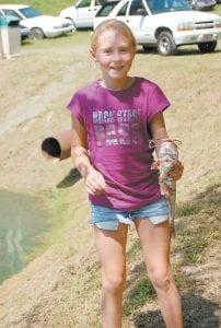 Deidra Banks, of Neon, held a catfi sh she caught at the kids' fishing event.