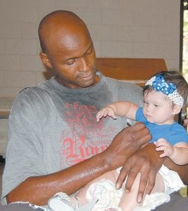 Former University of Kentucky basketball player Jules Camara autographed the shirt of seven-month-old Maggie Little on Aug. 27. Maggie is the daughter of Phillip and Beth Little of Whitesburg.
