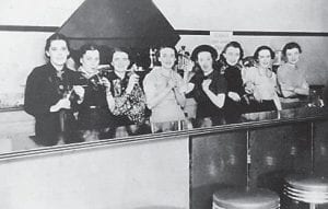 Those pictured were regulars at the Sweet Shop, left to right, Willa Maggard (later Hatter); Maude Day Lewis; Nan Lou Salling Lucas (later Lewis, then Enlow), the owner; Faye Collins Minton (later Goff ); Bernice Collins; Jesse Triplett Lewis; June Salling Webb (sister of Nan Lou); and Virginia Vermillion (later Pigman).