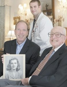"""Jim Purcell holds a photo of his late wife of 64 years, Dorothy """"Dot"""" Purcell, in his living room accompanied by his his son Mike Purcell, left, and Indiana University Northwest firstyear medical student Lucas Buchler. Dot Purcell wanted her body to go to science and she ended up at Buchler's school, which has an unusual program where medical students often meet the families of the donors they dissect in gross anatomy. Though reluctant at first, some of Purcell's family members, including her husband, ended up meeting Buchler and developing a friendship with him and a few other students. (AP Photo/M. Spencer Green)"""