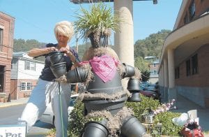 """FLOWERPOTS SPROUT ALL OVER TOWN — Earlene Williams worked on a flowerpot art figure titled """"The Pot That Called Kettle Black"""" in front of Community Trust Bank in Whitesburg earlier this week. Williams was putting finishing touches on the pot for the Kentucky Laureate Rho Chapter of Beta Sigma Phi sorority to which she belongs. Several other pieces of flowerpot art can be found in downtown Whitesburg this week as part of Mountain Heritage Festival activities. (Photo by Sally Barto)"""