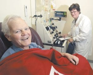 """Bob Svensson was hooked up to a blood infusion machine under the care of Nancy Grant, a registered nurse at the American Red Cross in Dedham, Mass., as he underwent a $93,000 prostate cancer treatment. The Provenge therapy, approved in April, adds four months' survival, on average, for men with incurable prostate tumors. Svensson is honest about why he got it: insurance paid. """"I would not spend that money,"""" because the benefit doesn't seem worth it, says Svensson, 80, a former corporate finance officer from Bedford, Mass. (AP Photo)"""
