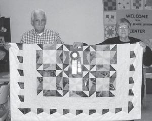 RIBBON WINNER — Coleene and Rhufort Hart display the quilt made by Mrs. Hart which won a blue ribbon and the overall championship ribbon.