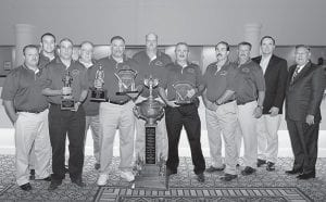 TOP RESCUE TEAM — The Black Mountain Resources Mine Rescue Team finished first in the Kentucky Mining Institute's Mine Rescue Contest held Sept. 9 in Lexington. Fifty teams representing eight states competed. Pictured are (left to right) Donnie Thomas, Kevin Harris, Tim Turner, Jack Quillen, Randy Watts, Raymond Sturgill, Don Walker, Eddie Spangler, Ronnie Biggerstaff , Ross Kegan, and Len Peters, who presented the championship trophies. The championship team has been in existence for less than three years. Turner and Lloyd were also first and second in the benchman competition, which deals with testing breathing apparatus and correcting malfunctions.